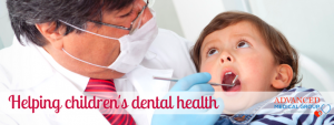 child in with dentist looking into his mouth